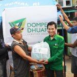 Manager Program Afrizal, saat memberikan paket bantuan sembako dan pakaian.